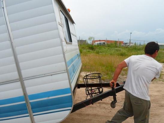 Empleados de EDIICO empujan la casa-rodante.